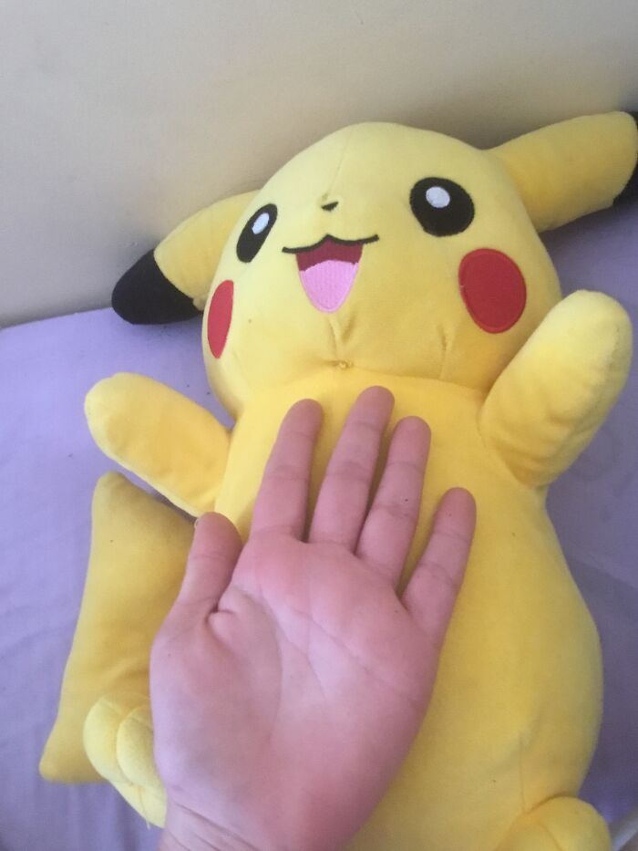 One Of My Favourite Things Is This Giant Pikachu With A Comparison To My 12-Year-Old Hand. I Got It From A Claw Machine.